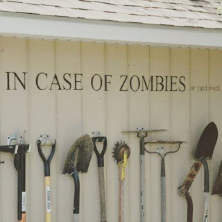 """Garden tools hung on a wall with the words """"In case of zombies or yard work"""" written over them."""