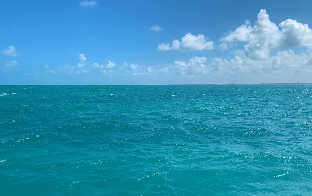 mar aberto esverdeado com ceu aberto com algumas nuvens ao fundo