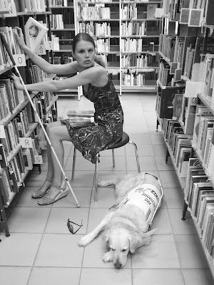 Linda sedí na židličce v knihovně, vyndavá knihu z regálu a díváce na ležícího retrívra Cilku