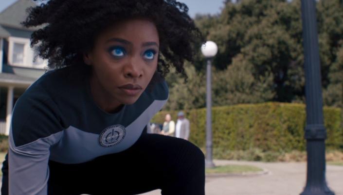 Imagem: Monica Rambeau, uma mulher negra com cabelos pretos longos e soltos, em um uniforme composto de uma blusa azul e cinza com um símbolo da S.W.O.R.D., uma espada rodeada por um círculo, e uma calça preta, ajoelhada na calçada do bairro em Westview, olhando para cima, os olhos brilhando azuis.