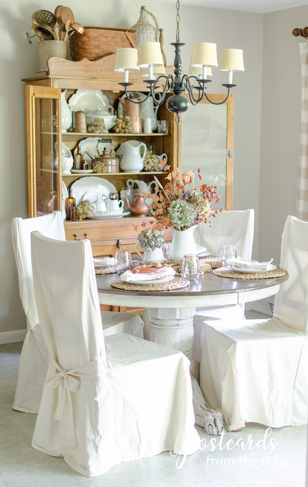 subtle fall table setting with faux and dried flowers and muted colors