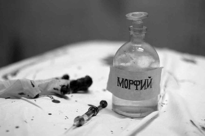 Флакон с морфием и шприц на столе