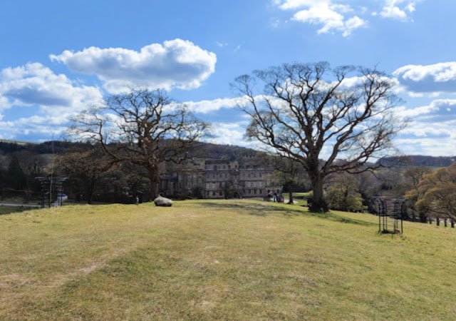 A large stately home sits at the bottom of a hill.  The path is leading to the house