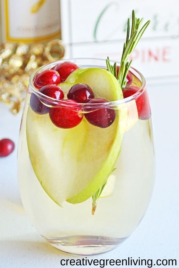 How to make easy sparkling white wine sangria with apples and cranberries. This is the best sangria to serve for a crowd at Christmas or winter holiday parties. Includes directions for a single glass or for a whole pitcher. This is the perfect easy to make cocktail for beginners that everyone will like.
