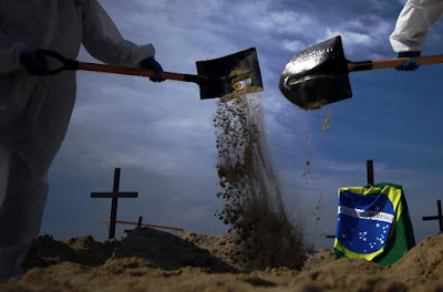 """The graves were dug in the memory of victims of the virus and to protest against Brazil's """"bad ...."""