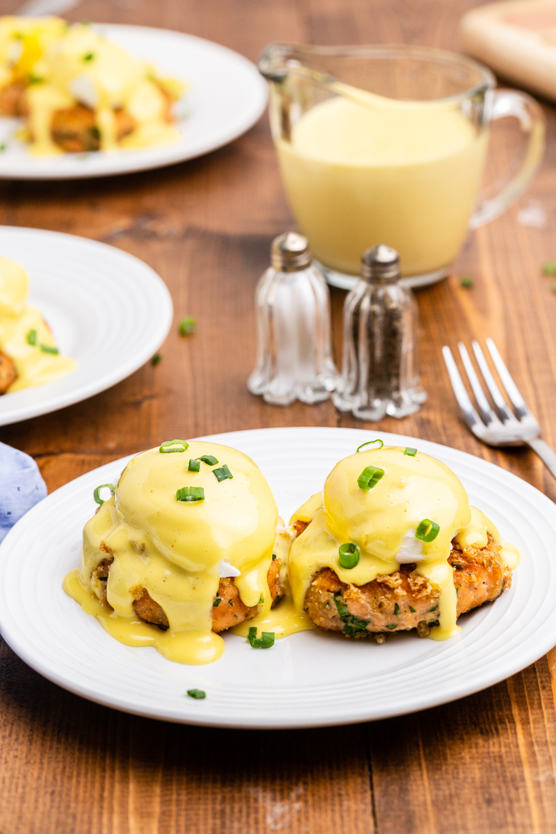 Keto Salmon Eggs Benedict on a white plate with fresh chopped chives on top.