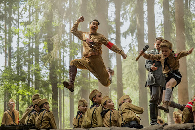 Jojo Rabbit movie scene where Jojo (Roman Griffin Davis) grabs a stick of dynamite and jumps over an embankment with his imaginary friend Hitler (Taika Waititi)