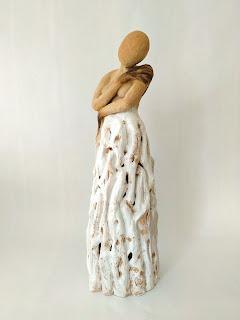 Escultura de cerámica de una mujer abrazándose