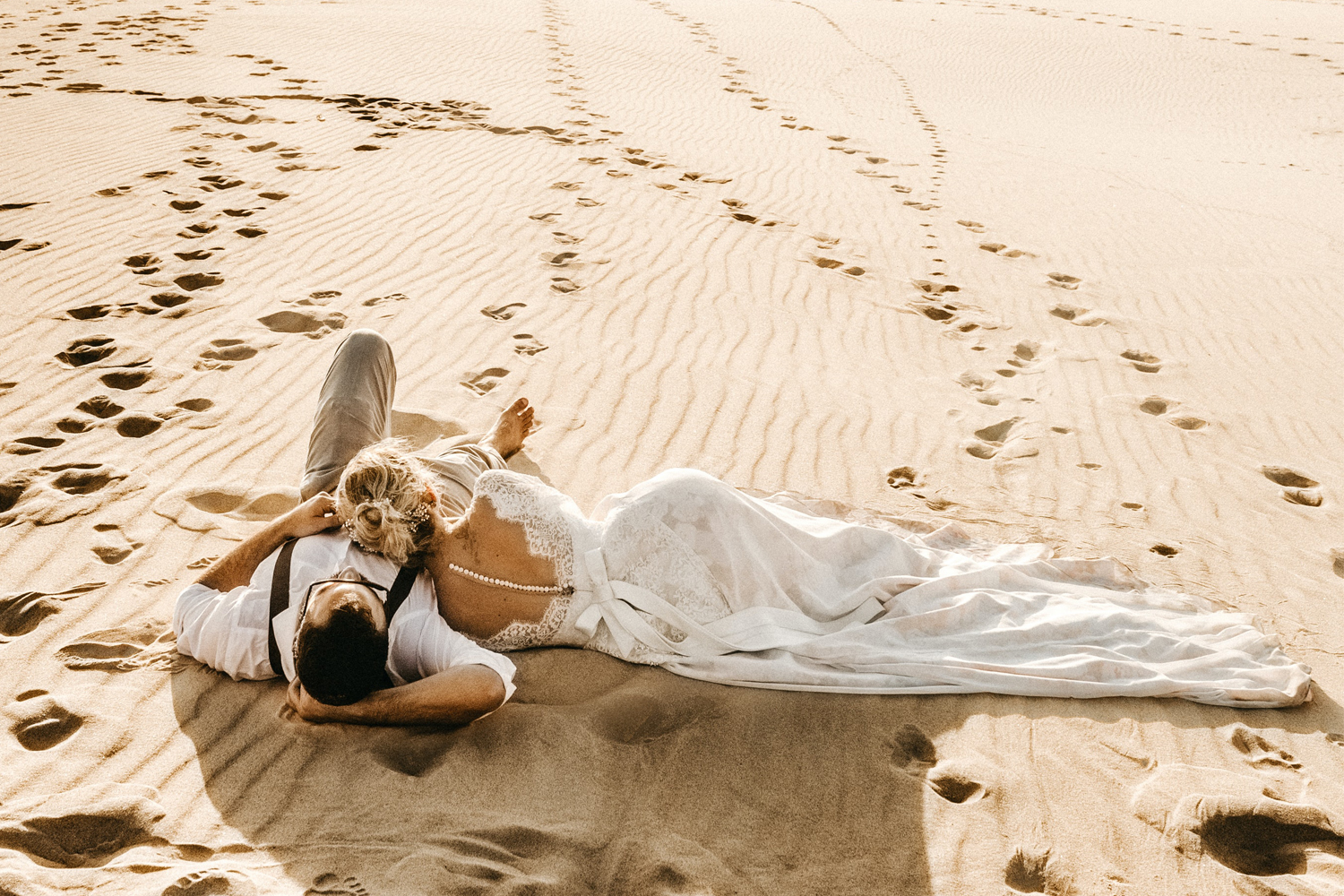 a couple in wedding attire laying on the beach