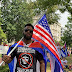 A Cuban American protester carries an American flag near the White House (Picture)