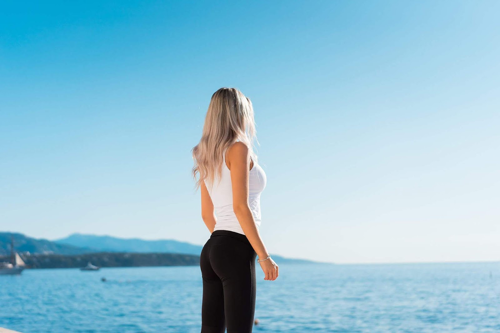donna in leggings e top che guarda verso il mare all'orizzonte