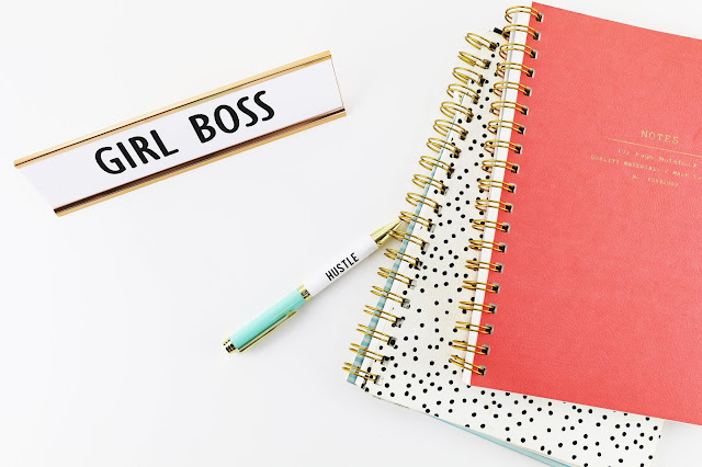 Flatlay showing a couple of notepads, a pen with hustle on the side and a desk sign that says 'girl boss'