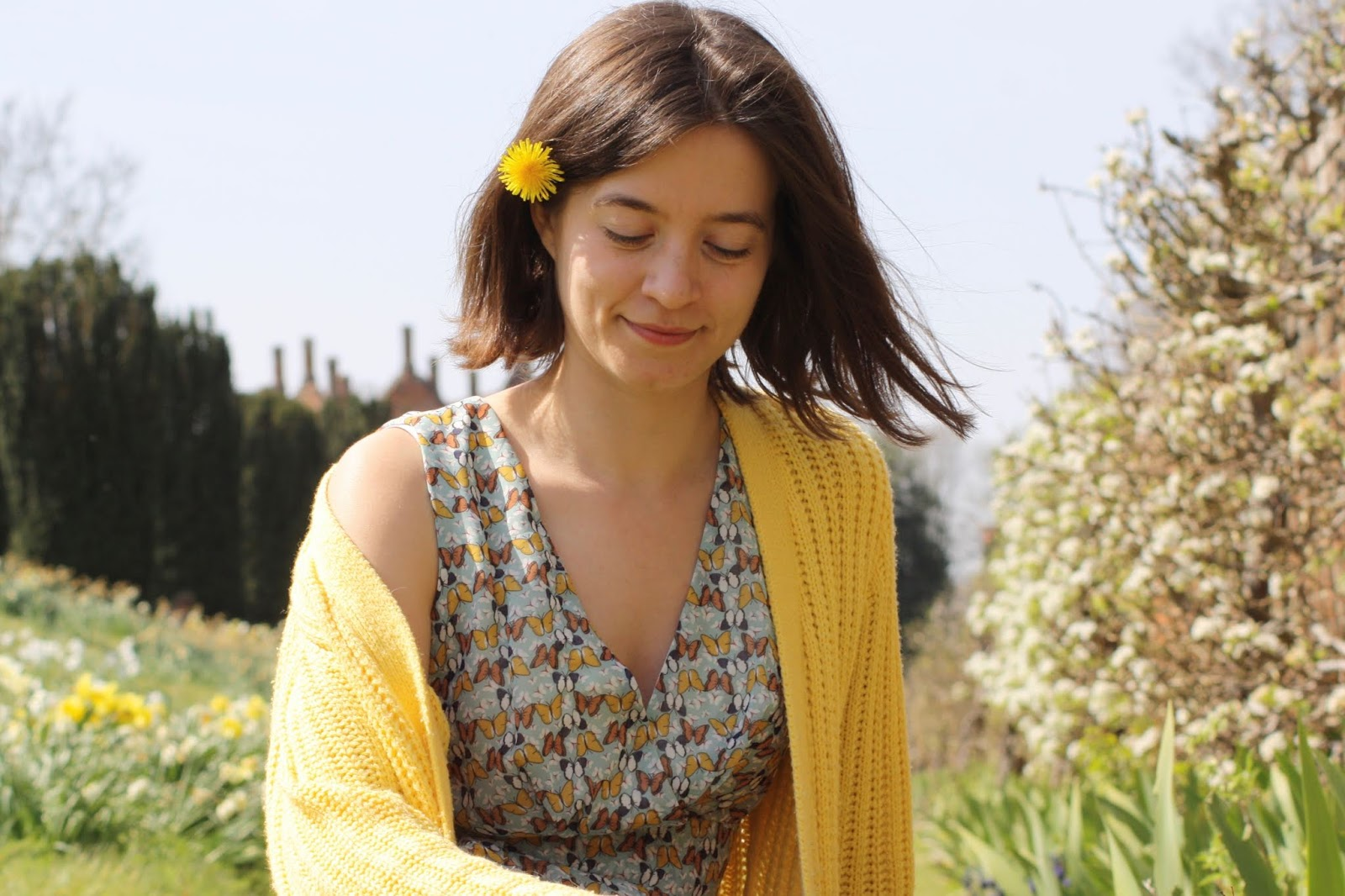 Abbey, wearing a butterfly print dress and yellow cardigan, smiles as she sits facing the camera with a dandelion tucked in her brown hair