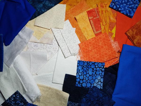 Blue, orange and white/cream fabric scraps | DevotedQuilter.com