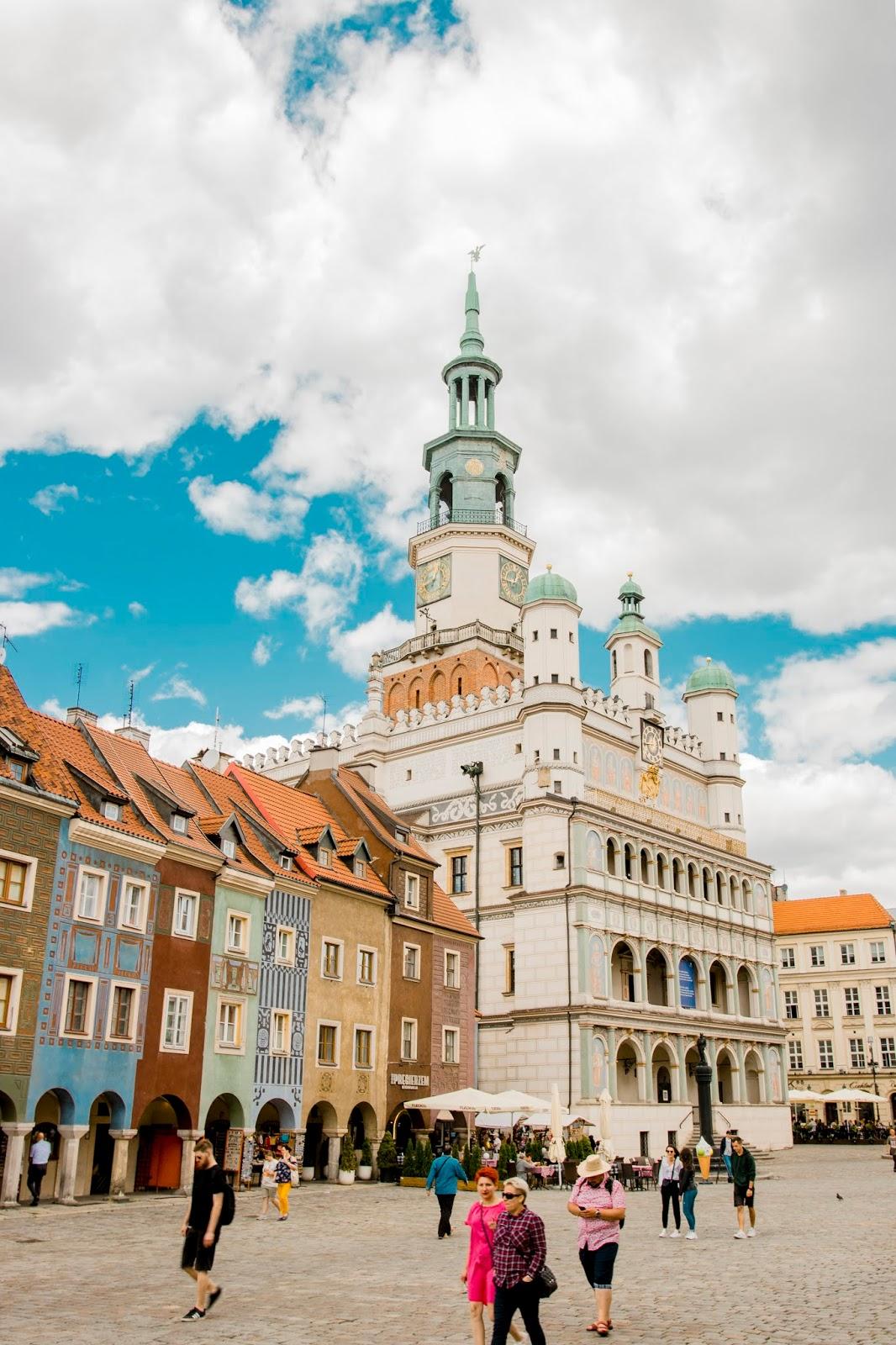 Renesansowy Ratusz stojący na środku poznańskiego Starego Rynku. Po jego lewej stronie kolorowe domki budnicze. Po bruku w cieniu ratusza przechadzają się turyści