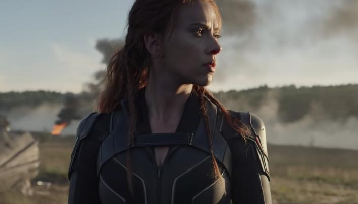 Imagem: a personagem Viúva Negra em um traje preto com detalhes vermelhos, ruiva e branca, com o rosto levemente sujo de fuligem e um rastro de destruição e explosão no fundo.