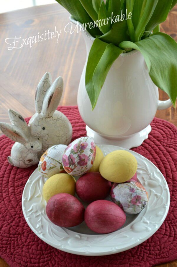 Decoupaged and painted Easter eggs on table with vase and bunny figures.