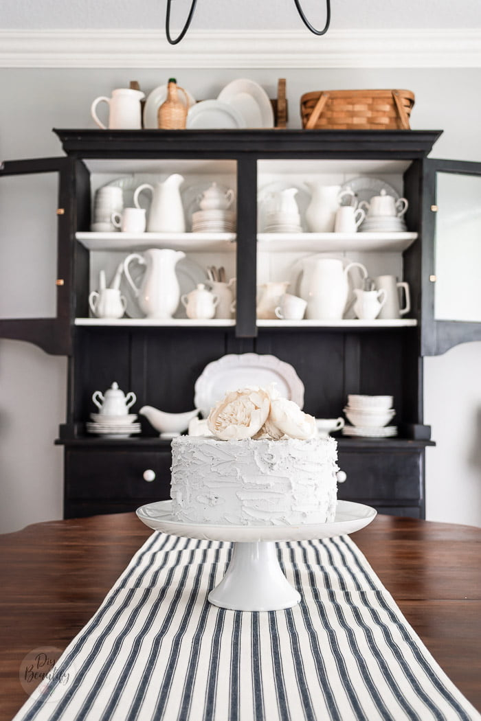 fake cake with wood flowers, black hutch and ironstone