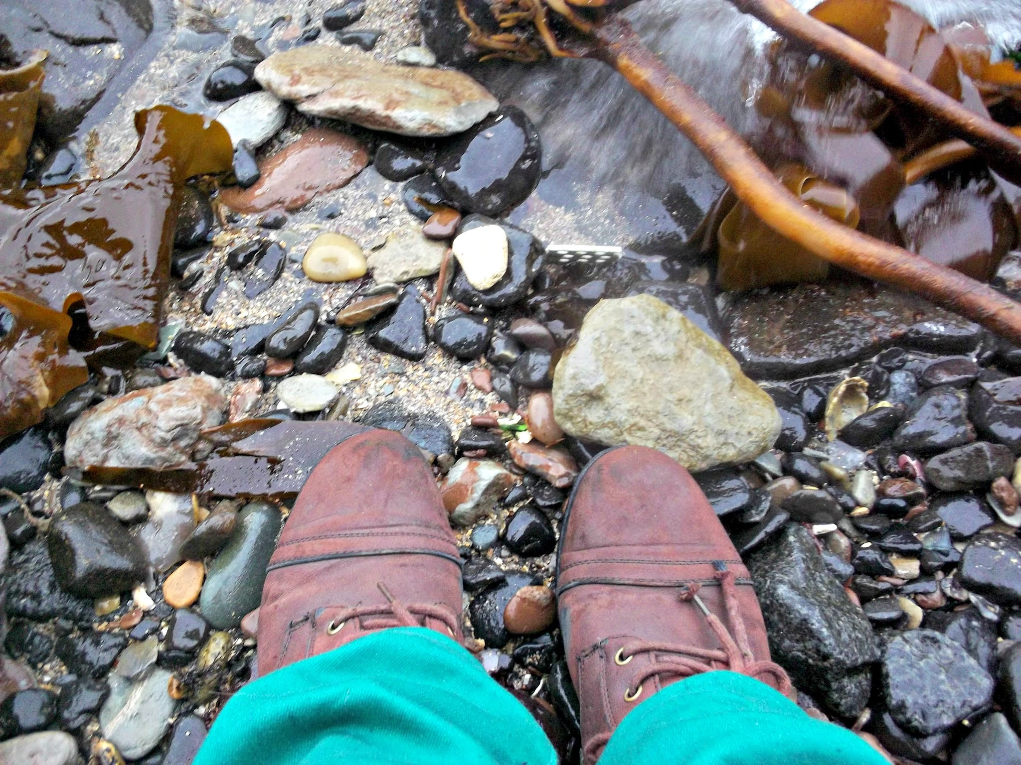 a pebble beach with brown boots and green jeans poking out on bottom edge of frame