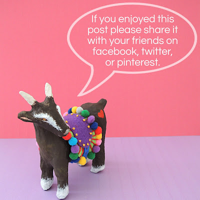paper mache goat with pom pom saddle blanket asking for social media shares