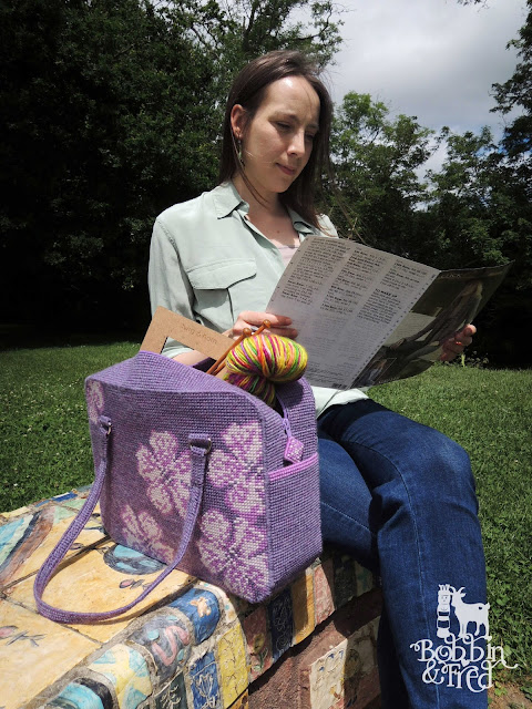 Woman reading sat next to her craft project bag in the park