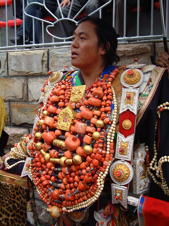 Khampa Tibetan man wearing numerous strings of beads and other ornaments during festival