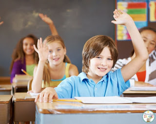 A boy raising his hand to answer a question. Having students raise their hand is an important routine to establish the beginning of the school year.