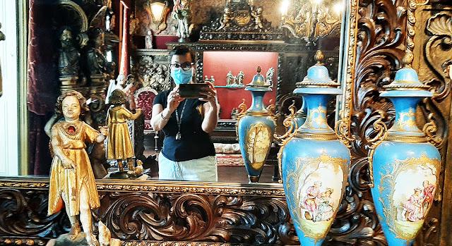 Selfie num espelho com moldura trabalhada, uma estárua e dois jarros de porcelana