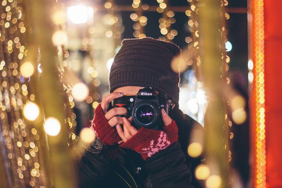 Девушка с фотоаппаратом между гирлянд