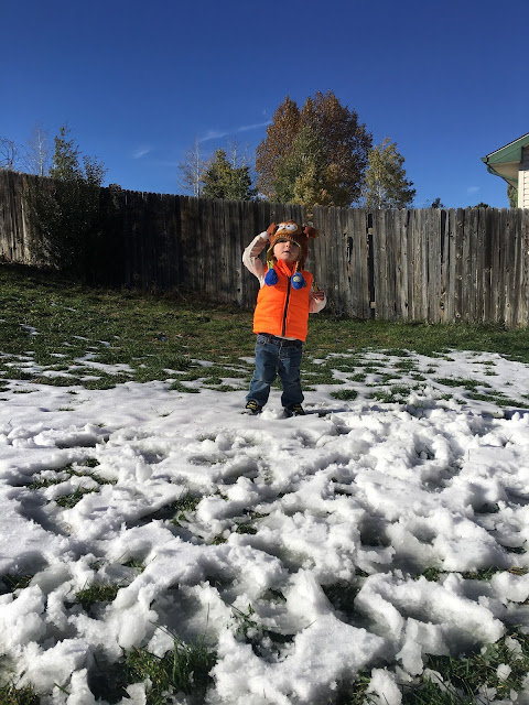 little boy, orange vest, snow on ground, blue sky