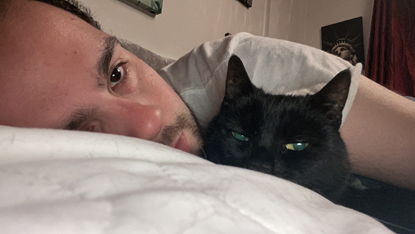 man and black cat laying in bed