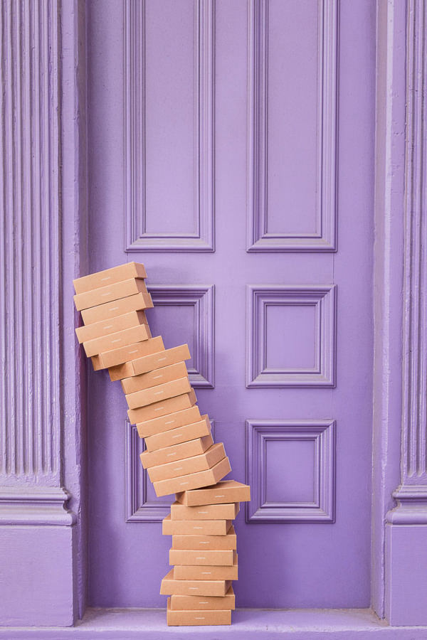 stack of boxes in front of a purple door