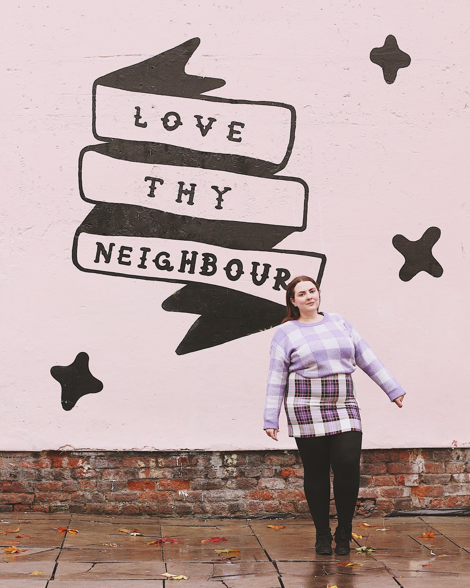 Becky stands in a purple checked jumper and skirt, in front of a pink wall with 'love thy neighbour' painted on as a mural