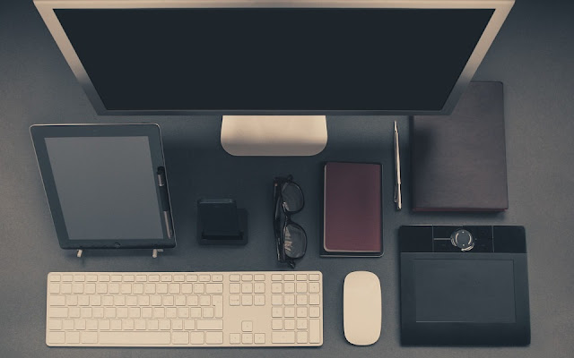 A monitor, tablet, smartphone, and other accessories on businessman's desk
