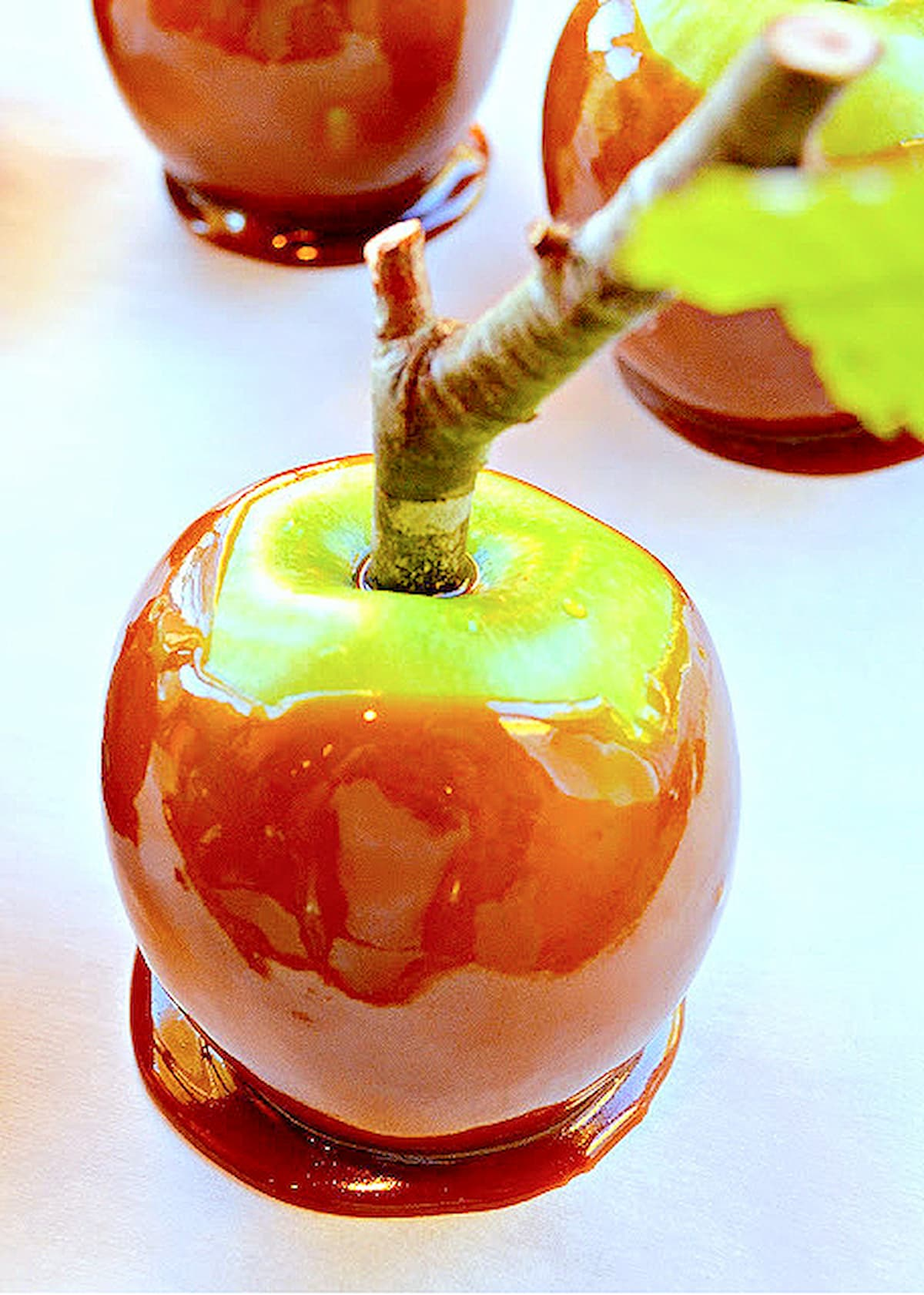Caramel Apples with a twig stuck in them for a handle on a piece of parchment paper.