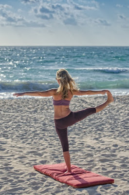 image of a woman stretching whilst standing one a mat, on the beach. Piriformis Syndrome and Piriformis Muscle Stretches