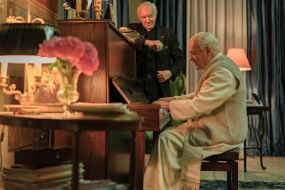"In Netflix's ""The Two Popes,"" Pope Benedict (Anthony Hopkins) plays the piano for Cardinal Jorge Bergoglio (Jonathan Pryce) during their private meeting"
