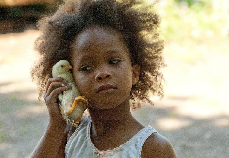 Quvenzhané Wallis as Hushpuppy outside holding a duck up to the side of her head like a telephone