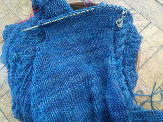 A dark blue sweater with the right front on a circular needle.  The other parts of the sweater are tucked in a yarn bowl under the right front.  The right front has been partially bound off for the armhole, and a single-twist cable runs along the other edge of the knitting.