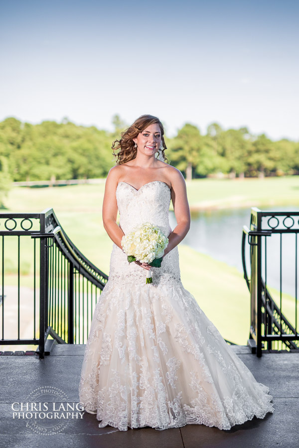Bride on the stairs in her wedding dress outside the clubhouse at River Landing