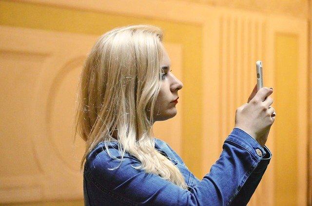 Seorang wanita yang sedang memegang ponselnya