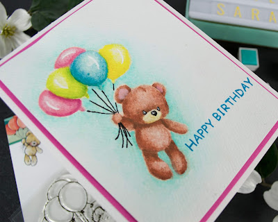Adorable Teddy Bear Image hanging beneath a bunch of balloons from Penny Black Stamps.  Image was stamped and colored in using no-line watercoloring with Altenew watercolors.
