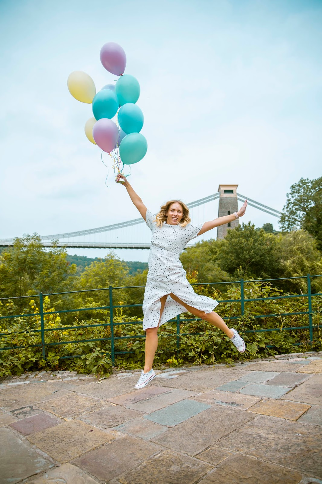 Rachel Emily in a White Midi Dress with Pastel Balloons by the Bristol Suspension Bridge Jumping
