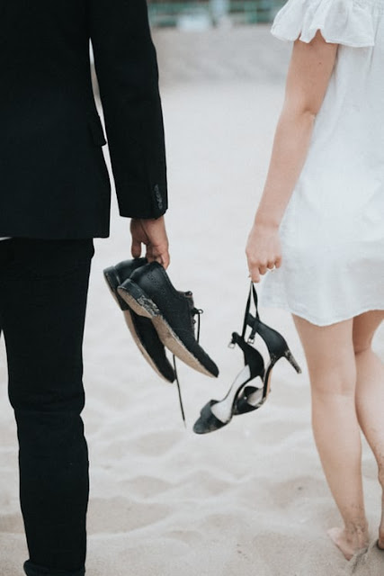 couple on their wedding day walking on beach holding shoes