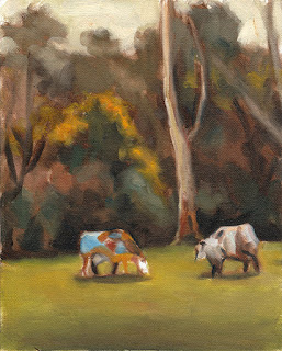 Oil painting of two multi-coloured cow-shaped sculptures in front of a forest of eucalypts and a flowering wattle.