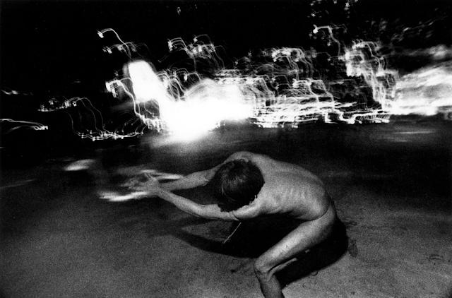A foto mostra um homem indígena rodopiando, ele está de costas para a câmera. A foto foi tirada em movimento e está em preto e branco. O homem aparenta ser magro e possui cabelo liso preto escuro. Ao fundo, se vê luzes acesas em movimento.