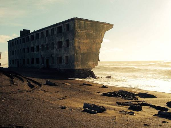 Abandoned apartment building being claimed by the sea in the former fishing village of Kirovsky, Russia.