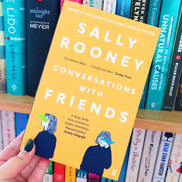 Conversations With Friends by Sally Rooney held up in front of bookshelf
