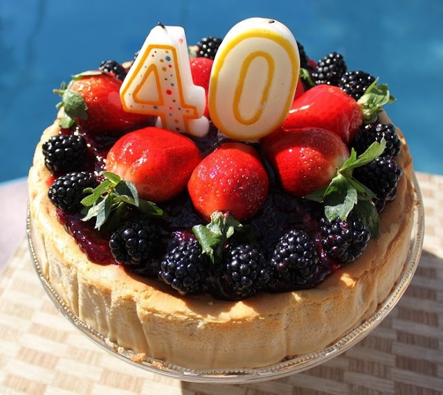 this is a cheesecake for a 40th birthday party called New York Cheesecake and has berries on top that are assorted.