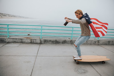 A young blond man with an American flag cape skateboarding along a cement boardwalk by the sea. Photo by Nathan Dumlao on Unsplash